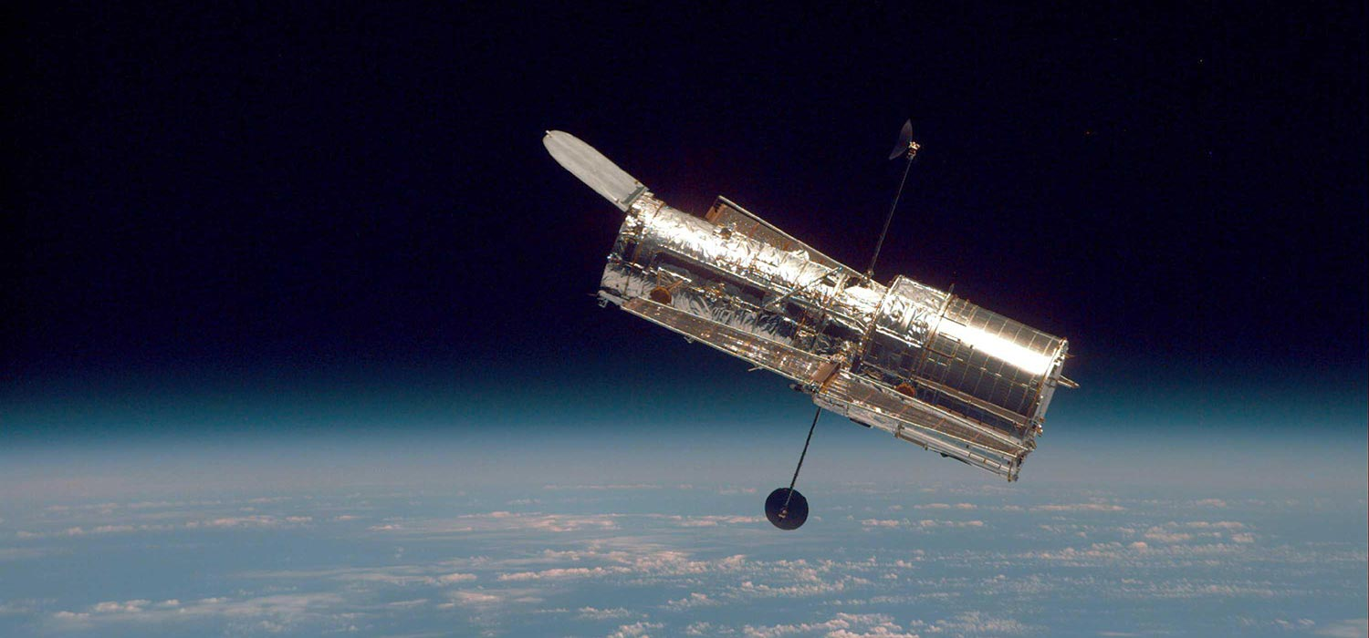 Image of the Hubble Space Telescope floating in space with Earth below.