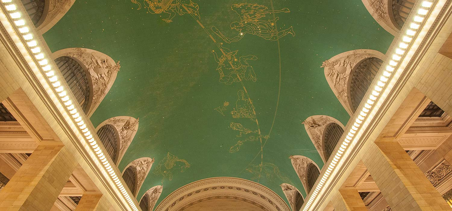 A photo of the green, vaulted ceiling of Grand Central, with illuminated stars and painted constellation figures.